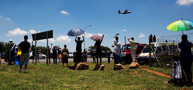 Des passants saluent l'avion qui transporte le cercueil de Nelson Mandela